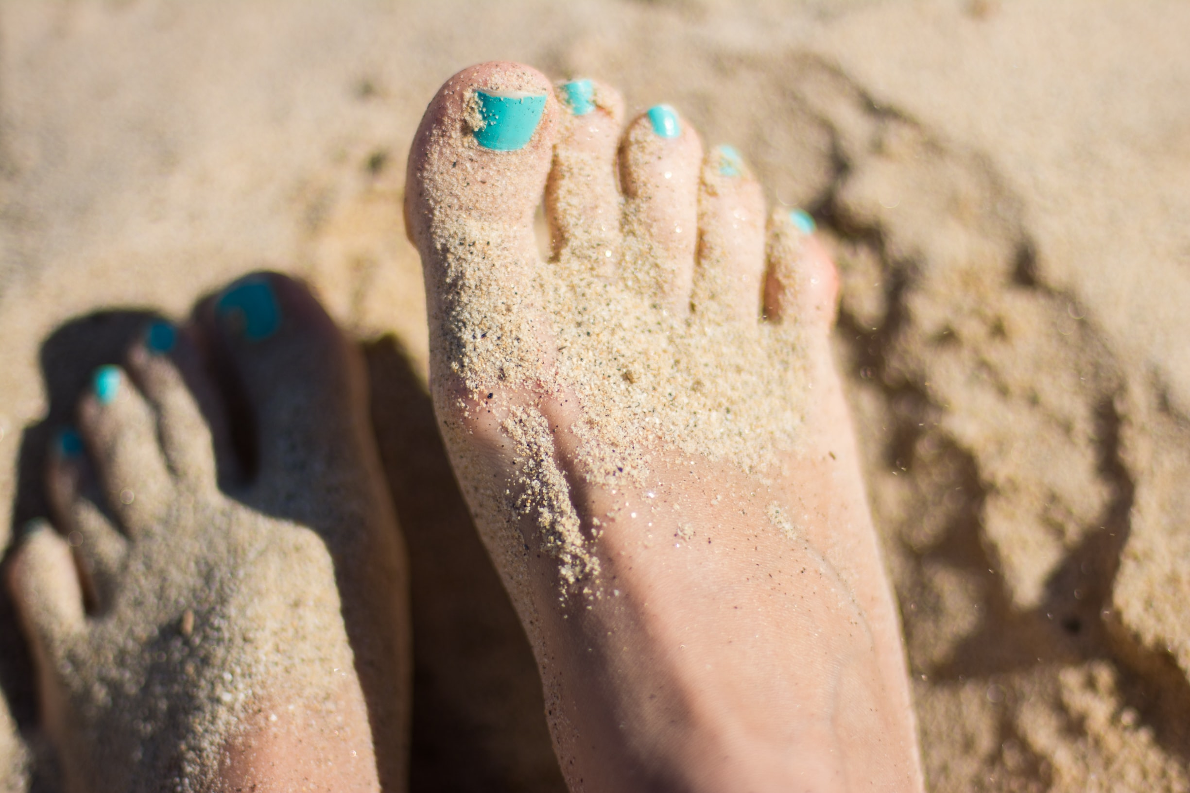 feet in the sand with blue toenails